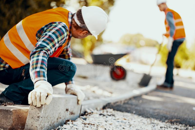 Trabajador con los guantes y en un casco que arregla encintados en la calle imagenes de archivo