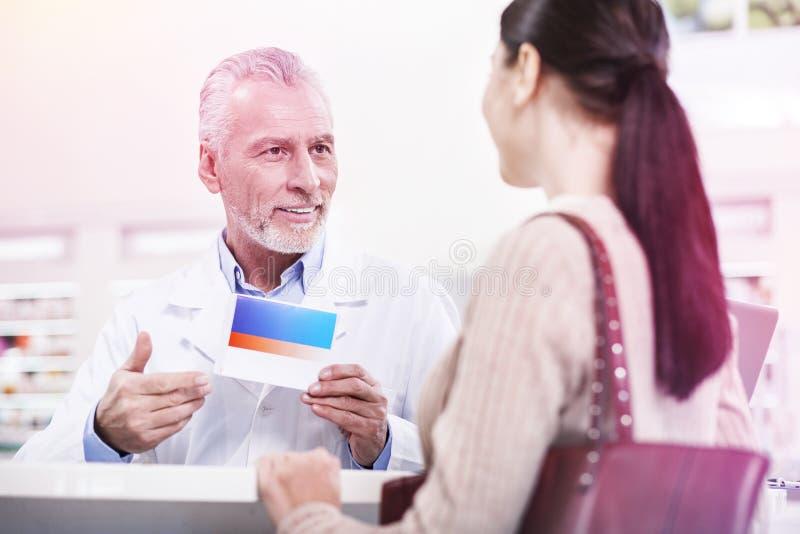 Trabajador confiado de la farmacia que ofrece la nueva medicación a una mujer imagen de archivo libre de regalías