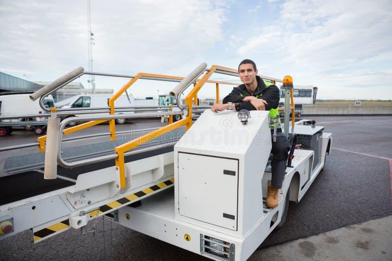 Trabajador confiado que se sienta en el camión del transportador del equipaje imágenes de archivo libres de regalías