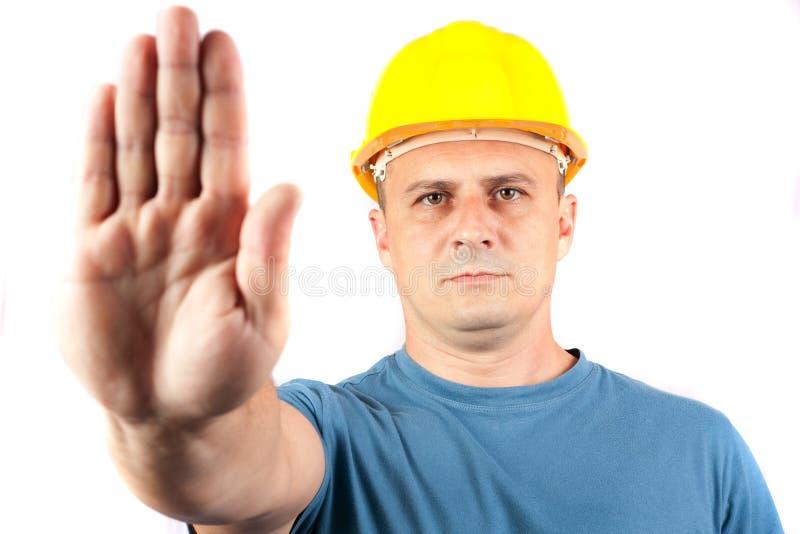 Trabajador de collar azul que hace una muestra de la parada fotografía de archivo