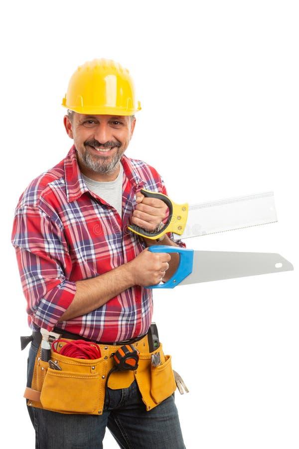 Trabajador de Constion que sostiene dos sierras foto de archivo