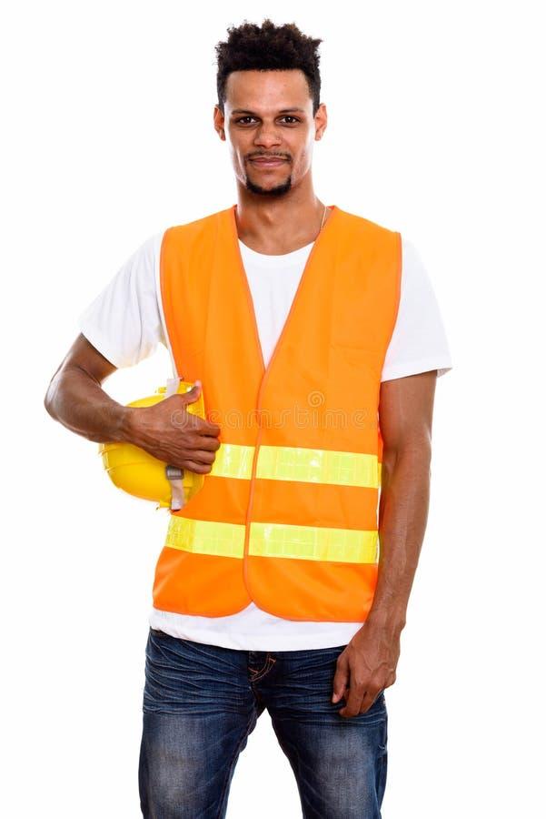 Trabajador de construcción africano joven del hombre que sostiene el casco de seguridad imagen de archivo libre de regalías