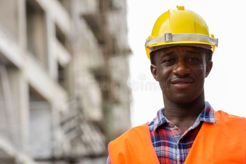 Trabajador de construcción africano negro feliz joven del hombre que sonríe en el bui fotografía de archivo