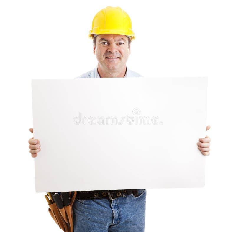 Trabajador de construcción cómodo con la muestra imagen de archivo libre de regalías