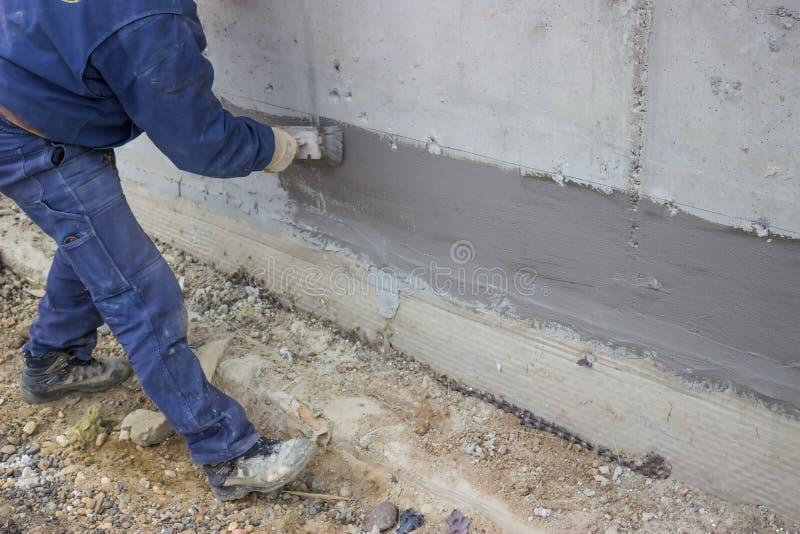 Trabajador de construcción con el aislamiento hidráulico aplicado del cepillo imagen de archivo libre de regalías