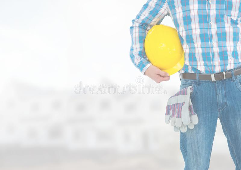 Trabajador de construcción con el casco de seguridad delante del emplazamiento de la obra foto de archivo