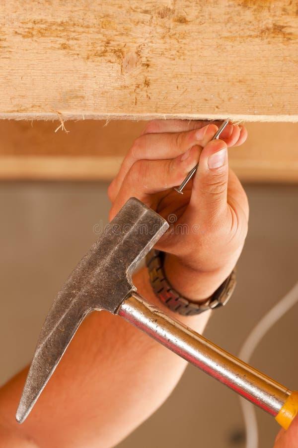 Trabajador de construcción con el martillo y el clavo fotos de archivo