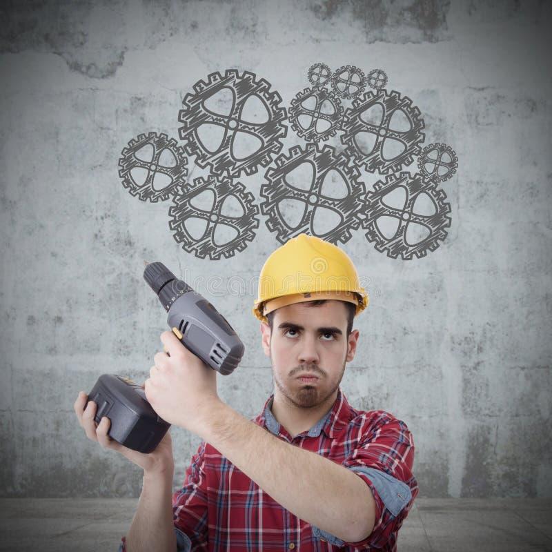 Trabajador de construcción con el pensamiento del taladro imagen de archivo libre de regalías