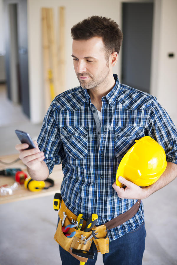 Trabajador de construcción con el teléfono elegante imagen de archivo
