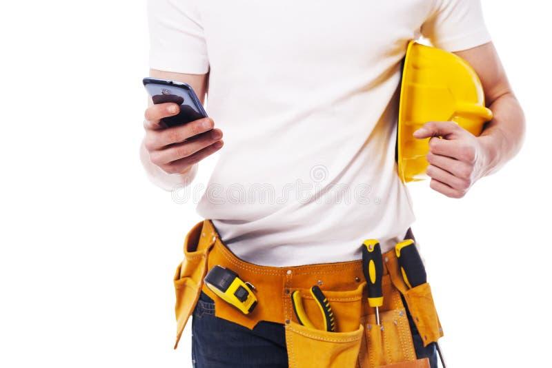 Trabajador de construcción con el teléfono móvil fotos de archivo libres de regalías