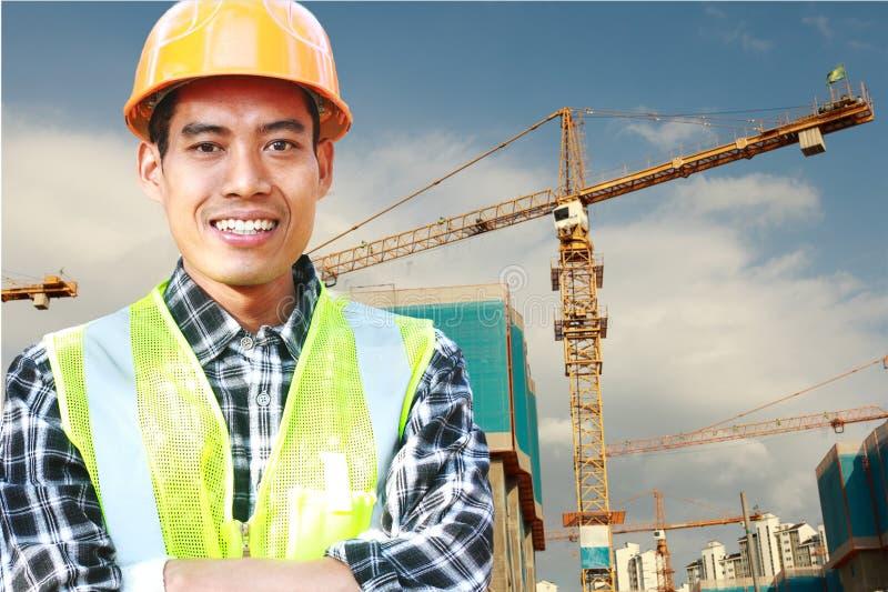 Trabajador de construcción con la grúa en la parte posterior fotografía de archivo