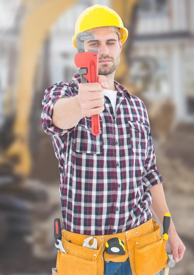Trabajador de construcción con la herramienta delante del emplazamiento de la obra foto de archivo libre de regalías