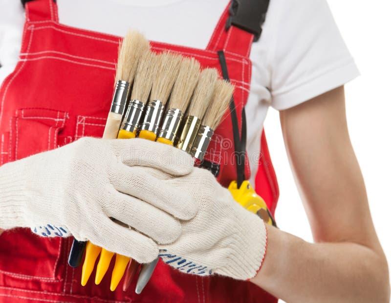 Trabajador de construcción con los cepillos imágenes de archivo libres de regalías