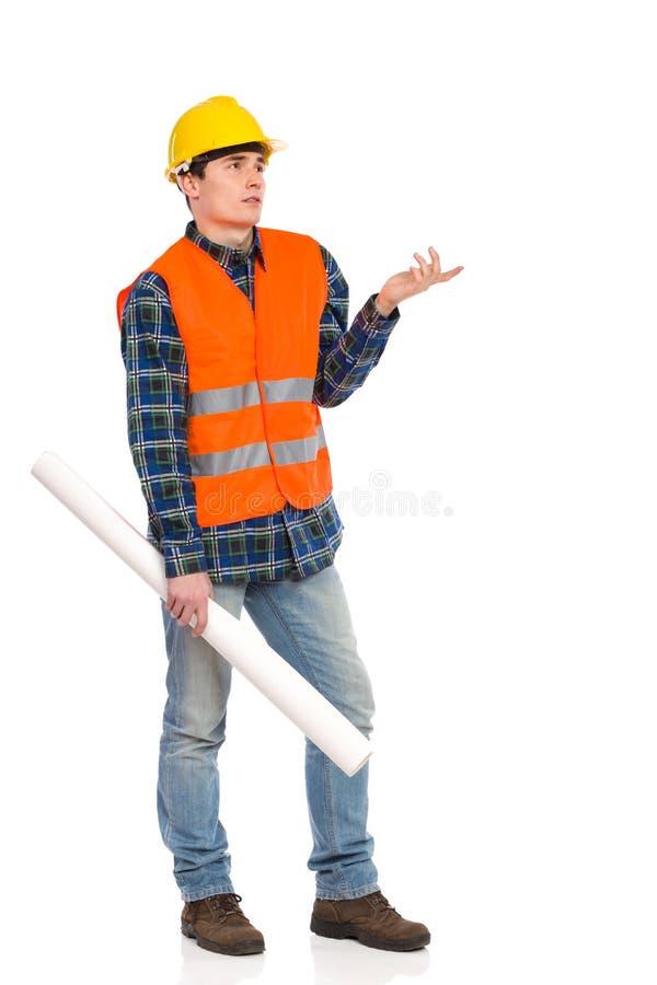 Trabajador de construcción confuso que lleva a cabo plan del papel rodado. foto de archivo