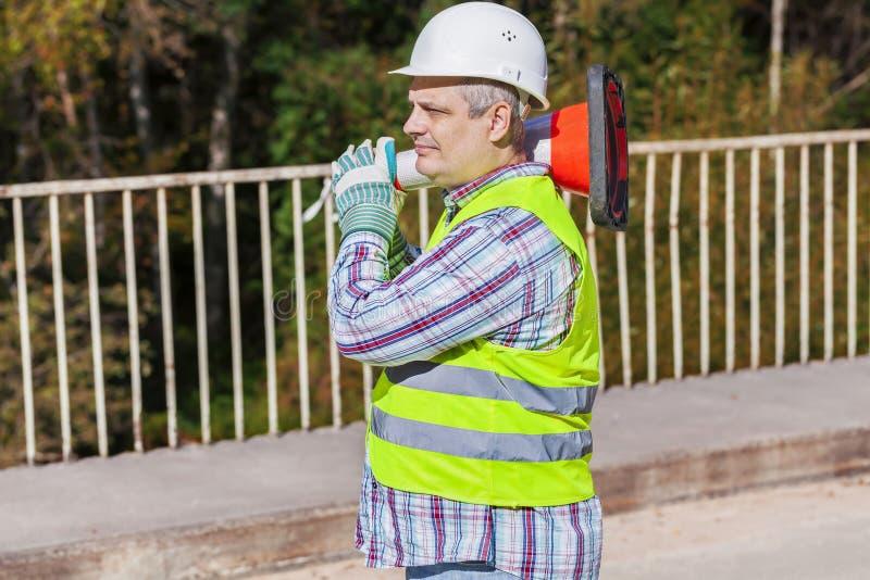 Trabajador de construcción de carreteras con el cono del tráfico en el puente imágenes de archivo libres de regalías