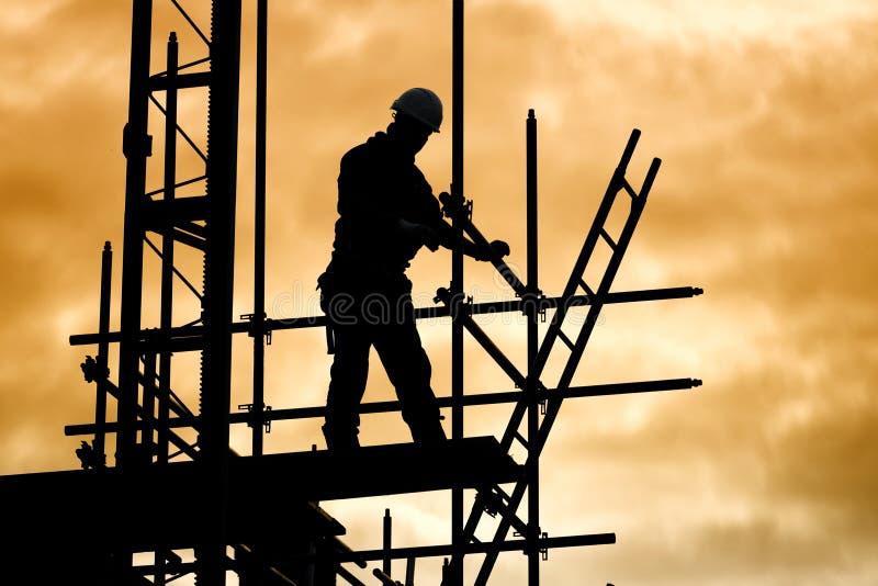 Trabajador de construcción de la silueta en solar del andamio fotos de archivo libres de regalías