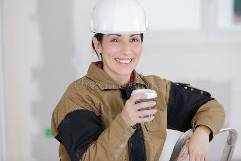 Trabajador de construcción de sexo femenino sonriente que tiene descanso para tomar café imágenes de archivo libres de regalías