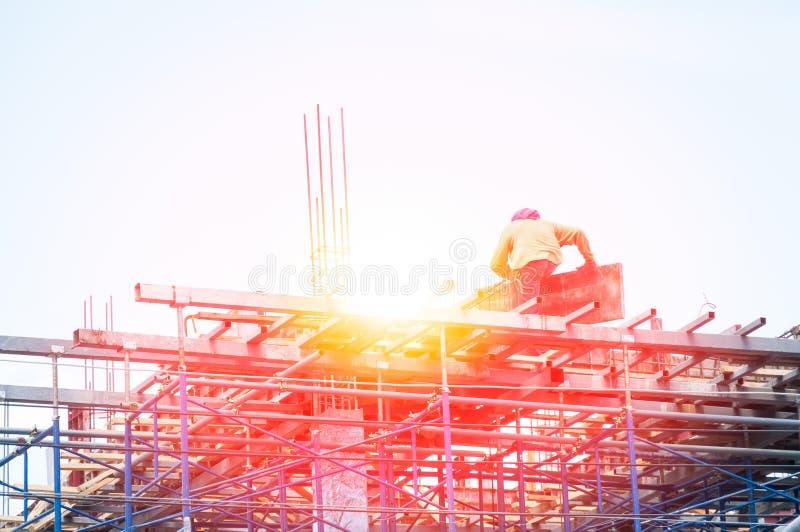 Trabajador de construcción durante trabajo del refuerzo con las barras del rebar del metal en el solar fotografía de archivo libre de regalías