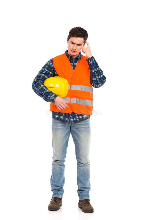Trabajador de construcción en casco amarillo y el chaleco anaranjado que rasguñan la cabeza. fotos de archivo