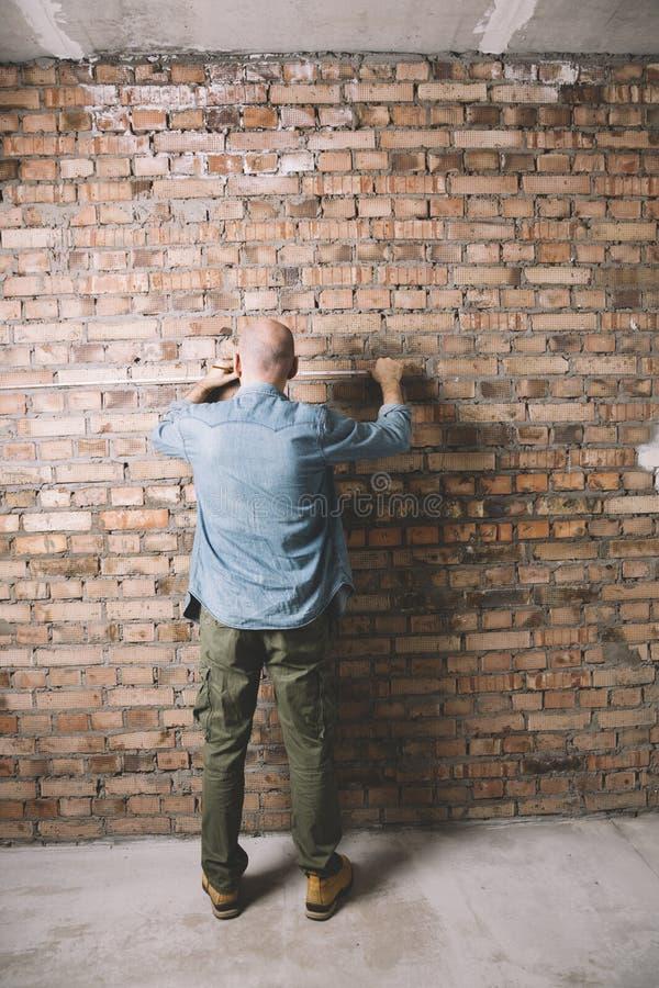 Trabajador de construcción en el fondo de la pared de ladrillo foto de archivo libre de regalías