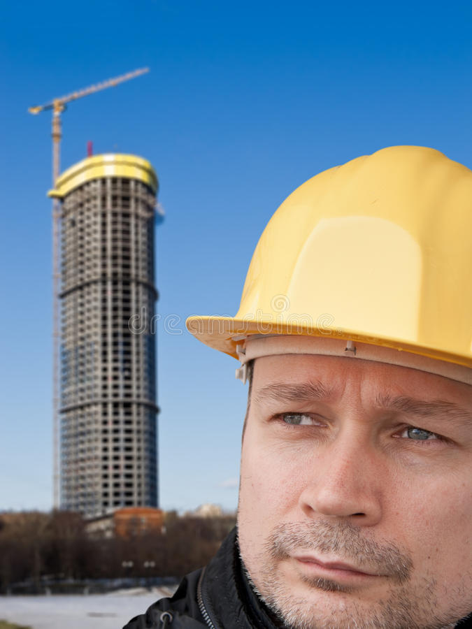 Trabajador de construcción en un casco amarillo fotos de archivo