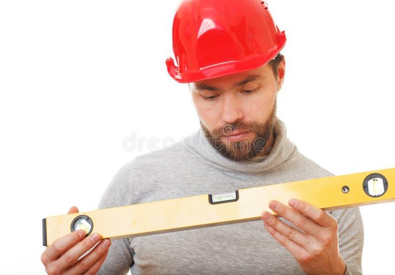 Trabajador de construcción en un casco rojo imagen de archivo libre de regalías