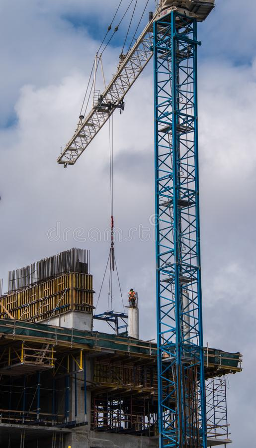 Trabajador de construcción encima del pilar concreto con la grúa fotos de archivo libres de regalías