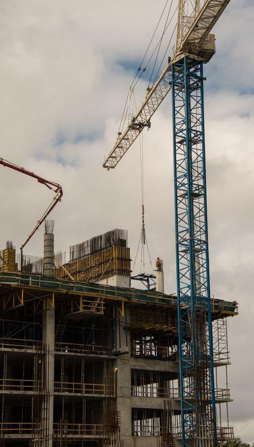 Trabajador de construcción encima del pilar concreto con la grúa fotografía de archivo libre de regalías