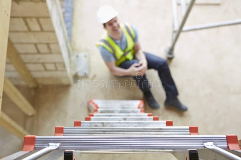 Trabajador de construcción Falling Off Ladder y pierna de la herida fotografía de archivo libre de regalías