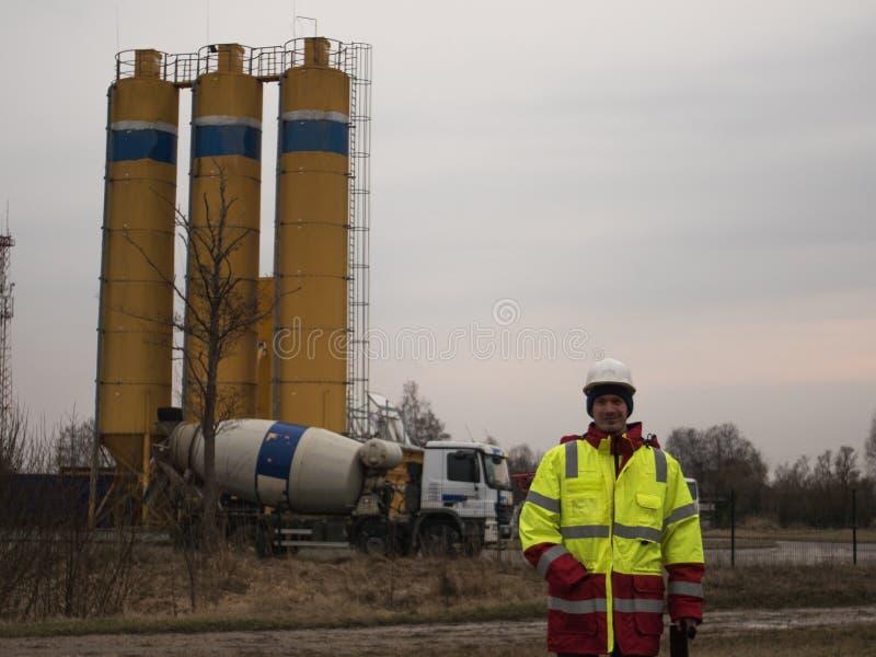 Trabajador de construcción feliz Constructor en casco y chaqueta reflexiva en el emplazamiento de la obra fotos de archivo