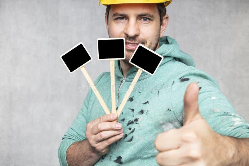 Trabajador de construcción feliz que sostiene una pizarra con el espacio para el texto o el texto, espacio de la copia fotografía de archivo libre de regalías