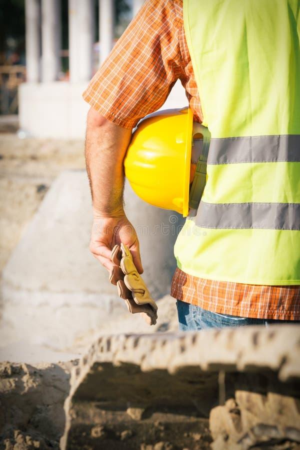 Trabajador de construcción Holding Yellow Hardhat fotografía de archivo