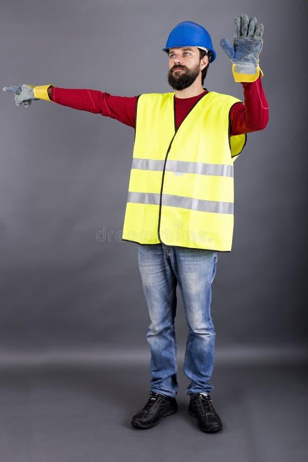 Trabajador de construcción joven con el tráfico de dirección del casco de protección, showin imagenes de archivo
