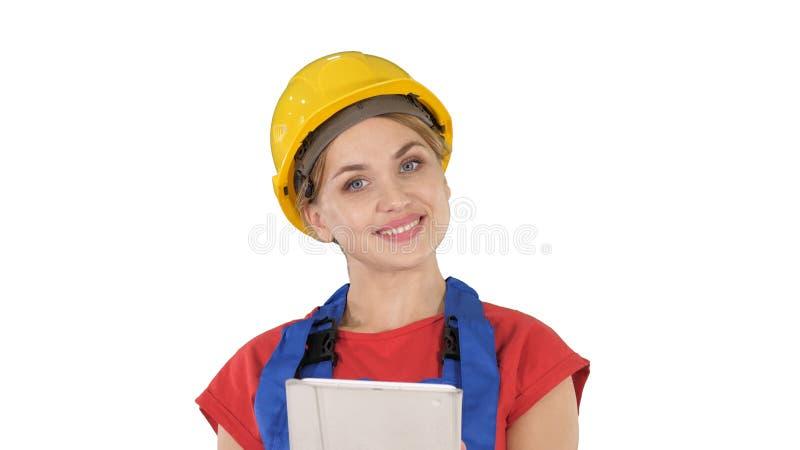 Trabajador de construcción joven con la tableta que presenta algo en el fondo blanco imagen de archivo