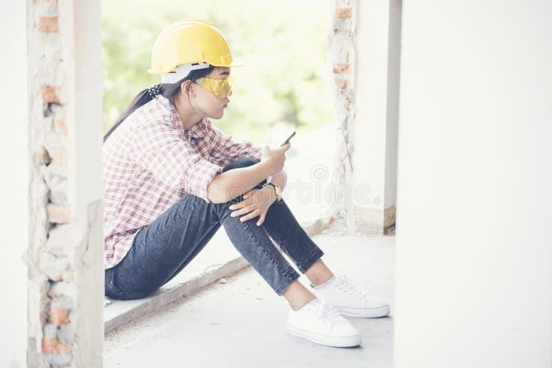 Trabajador de construcción joven que celebra el teléfono y el sittin elegantes en el emplazamiento de la obra Ingeniero hermoso j fotos de archivo