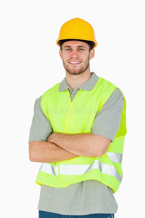Trabajador de construcción joven sonriente con los brazos plegables fotografía de archivo