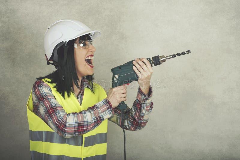 Trabajador de construcción de la mujer que celebra un taladro adentro sus manos fotografía de archivo libre de regalías