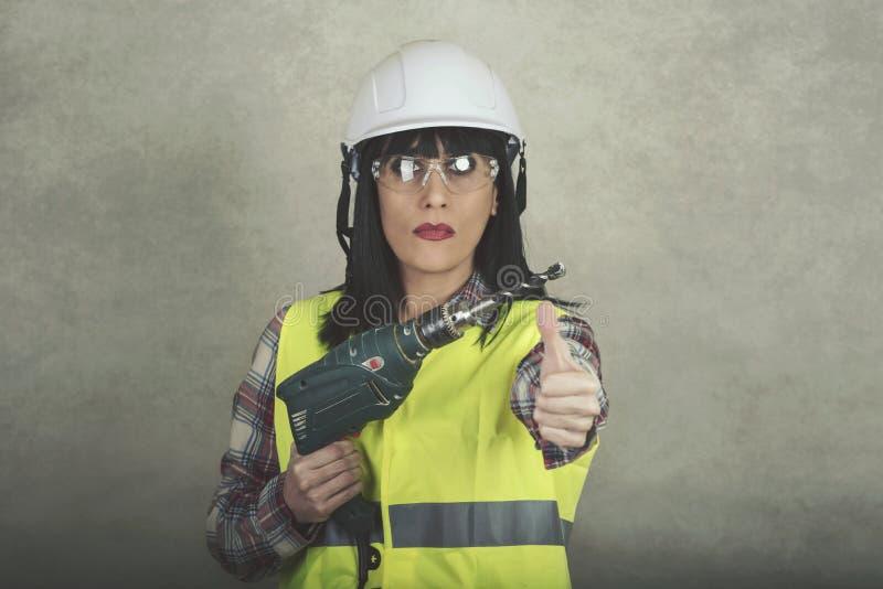 Trabajador de construcción de la mujer que celebra un taladro adentro sus manos imagenes de archivo
