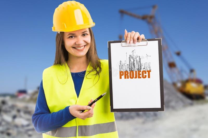 Trabajador de construcción de la mujer que presenta proyecto sobre el tablero foto de archivo libre de regalías
