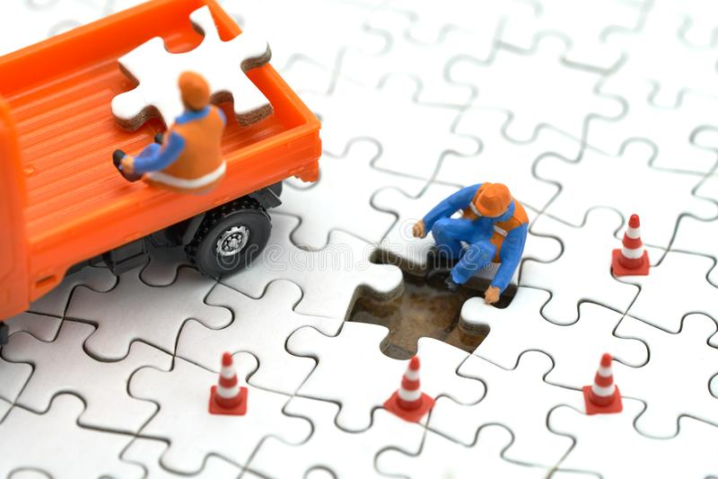 Trabajador de construcción miniatura de la gente en el rompecabezas blanco el usar como concepto del negocio del fondo y concepto fotografía de archivo libre de regalías