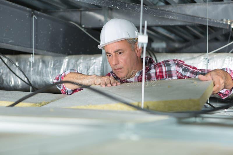 Trabajador de construcción que aísla termalmente el ático de la casa con lanas minerales fotos de archivo