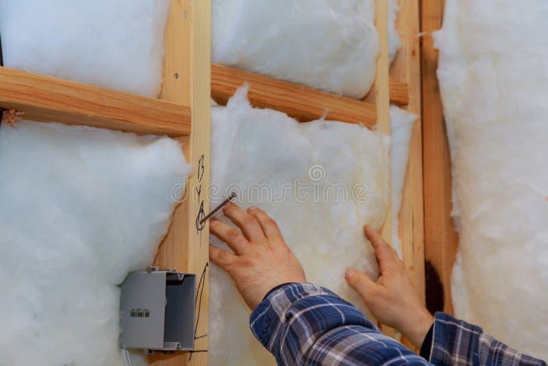 Trabajador de construcción que aísla termalmente la casa de marco de madera con las placas de madera de la fibra y el aislamiento fotografía de archivo