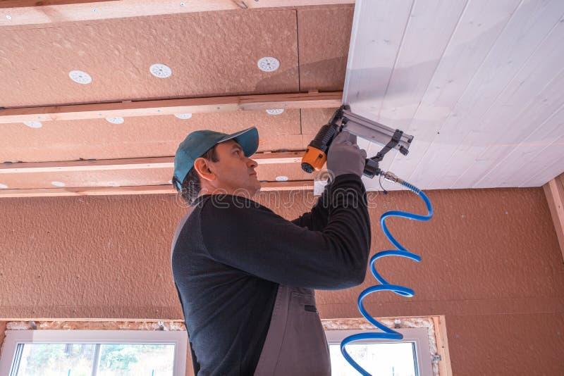 Trabajador de construcción que aísla termalmente la casa de marco de madera del eco imagen de archivo
