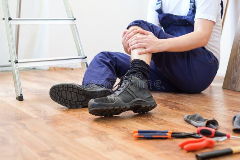 Trabajador de construcción que cae abajo la escalera imagenes de archivo