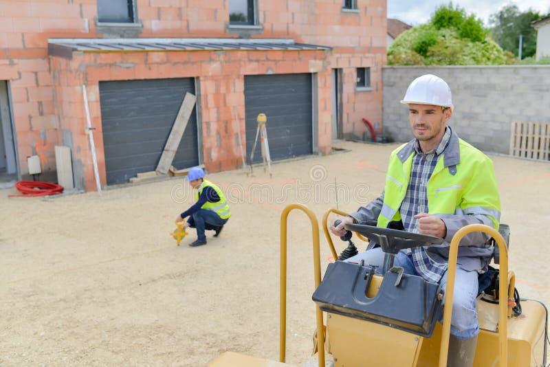 Trabajador de construcción que conduce la apisonadora de vapor imagenes de archivo