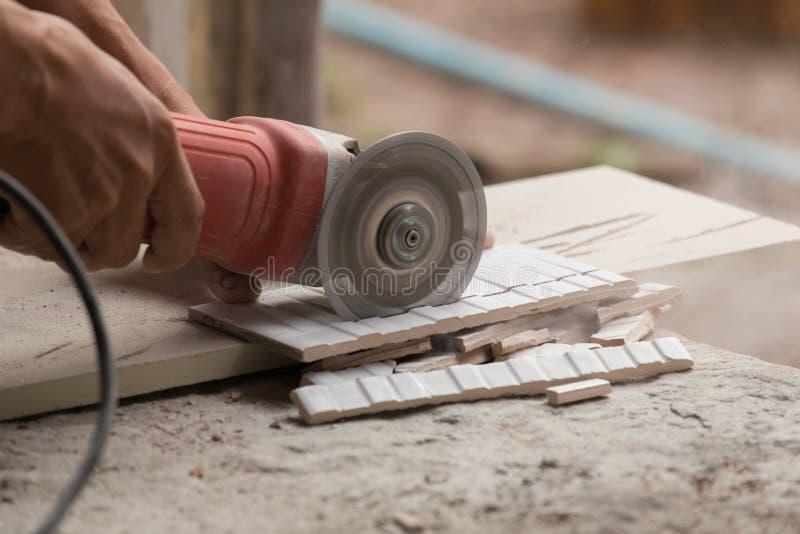 Trabajador de construcción que corta una teja usando una amoladora de ángulo foto de archivo