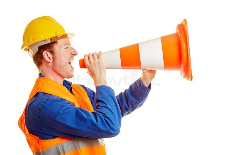 Trabajador de construcción que grita con un cono del tráfico imagen de archivo libre de regalías