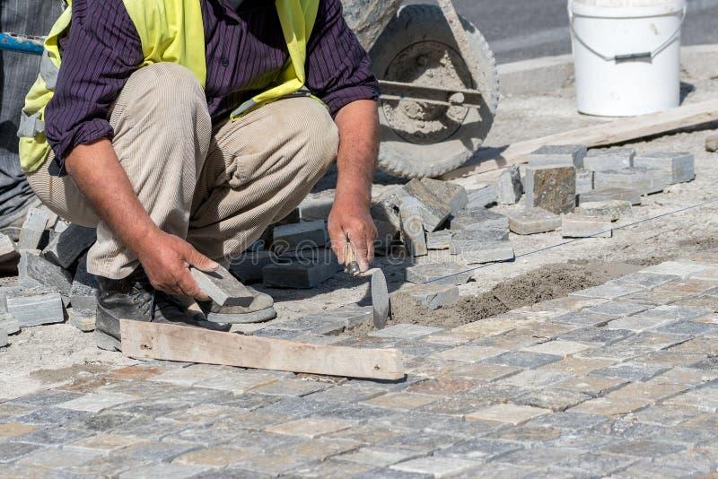 Trabajador de construcción que instala bloques de la piedra imagen de archivo libre de regalías