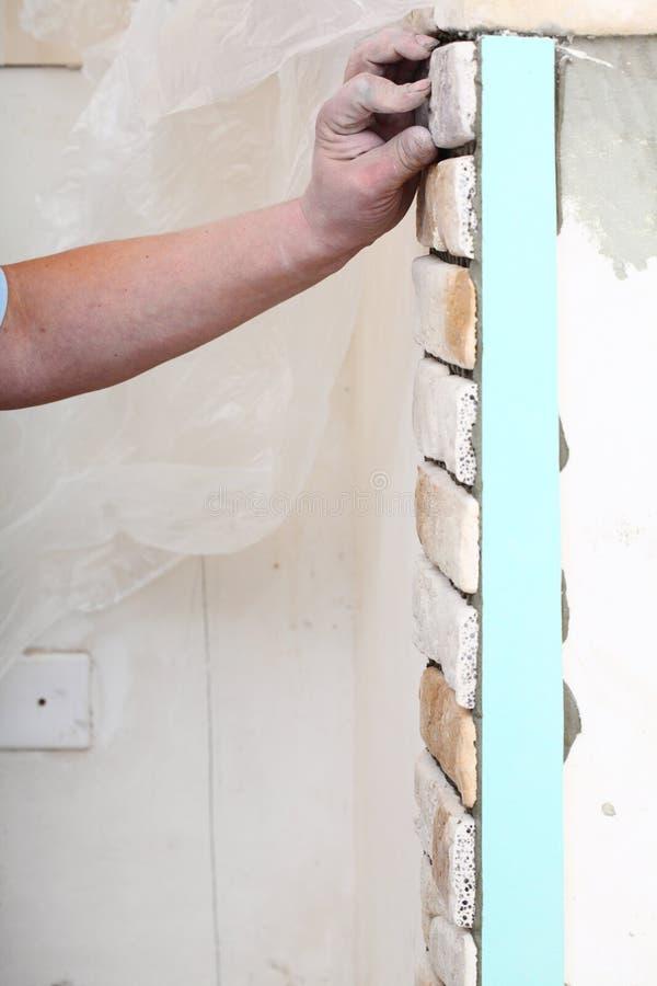 Trabajador de construcción que instala el ladrillo de las tejas en una pared imagenes de archivo