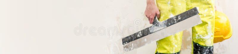 Trabajador de construcción que lleva a cabo el cuchillo de masilla y la imagen cosechada casco de protección fotografía de archivo